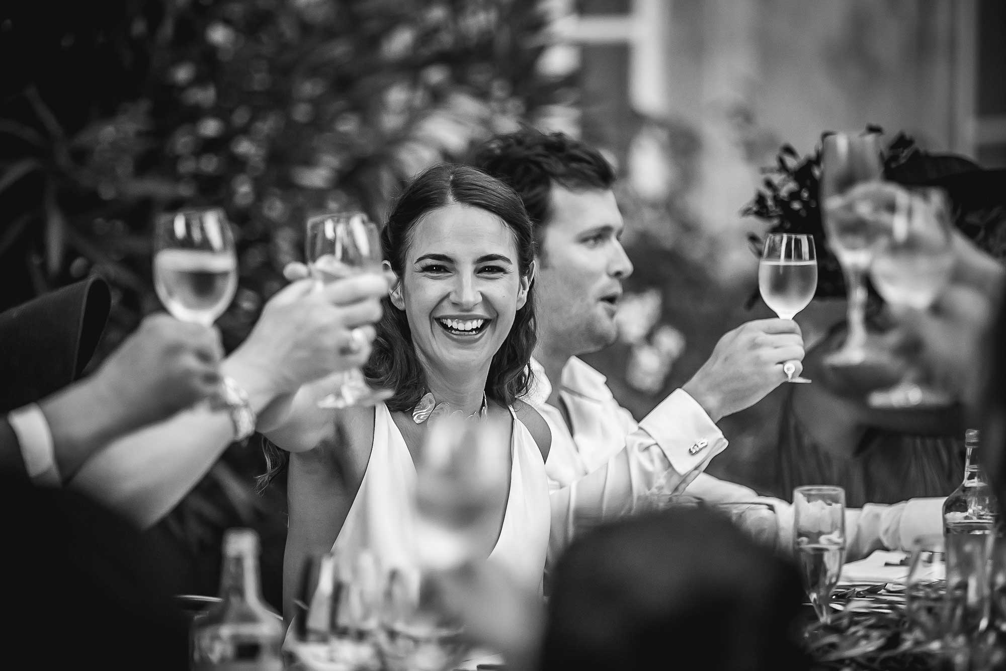 bride lifts glass to toast