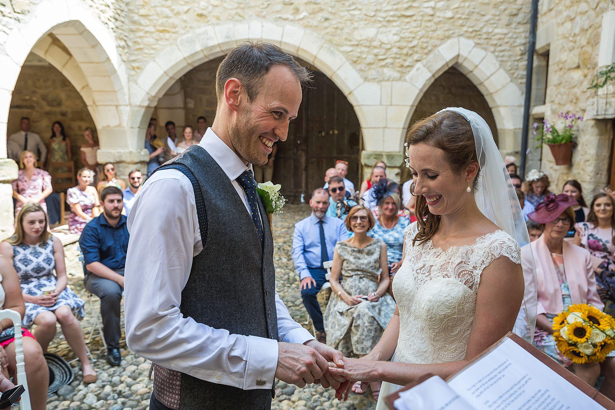 groom puts ring on brides finger