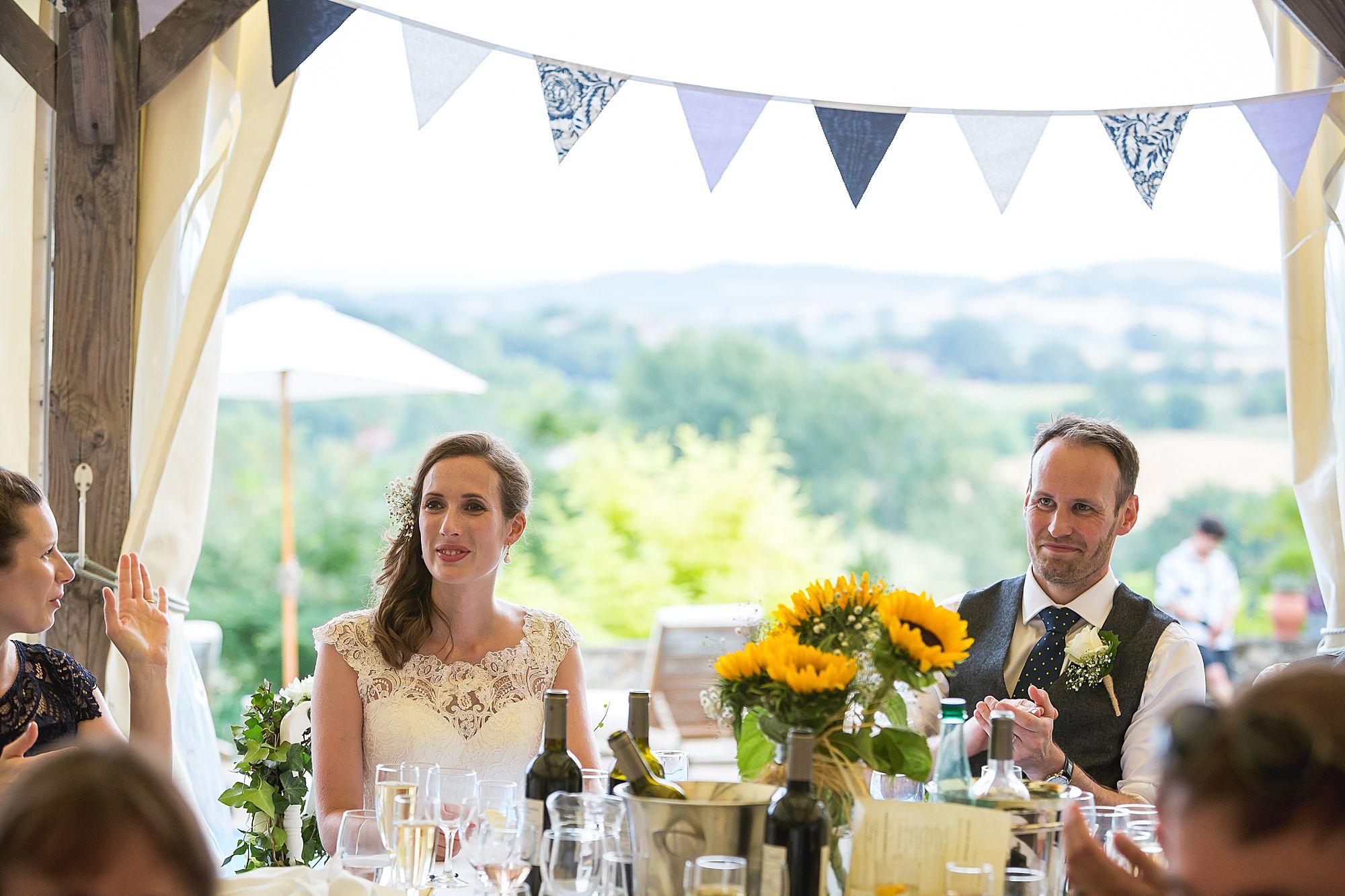 bride and groom listen to speech