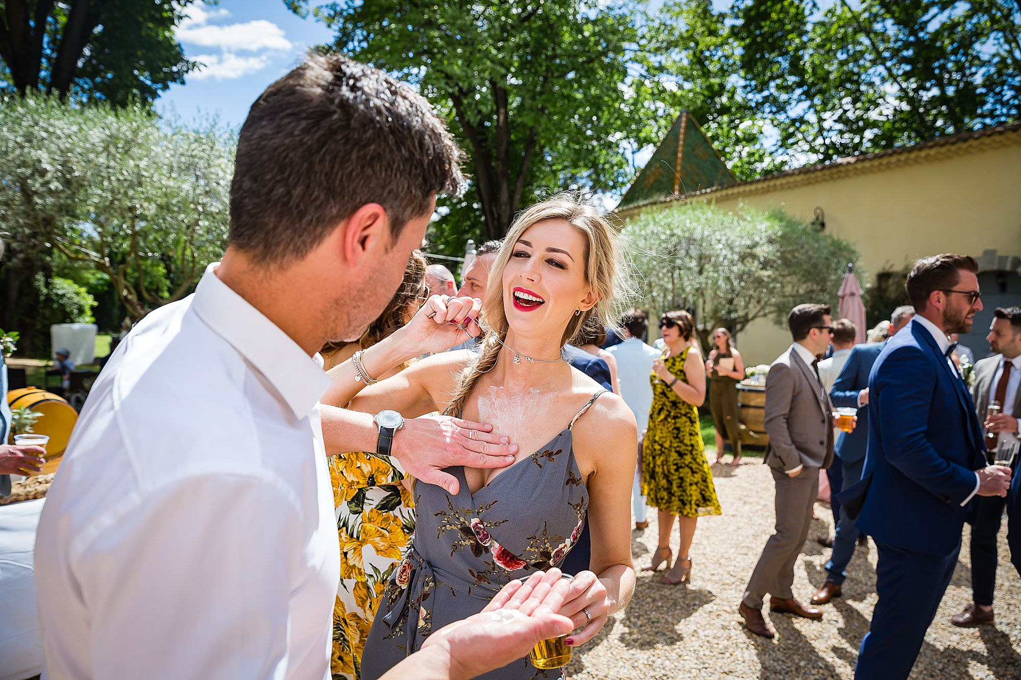 rubbing on suntan cream at Chateau Rieutort wedding