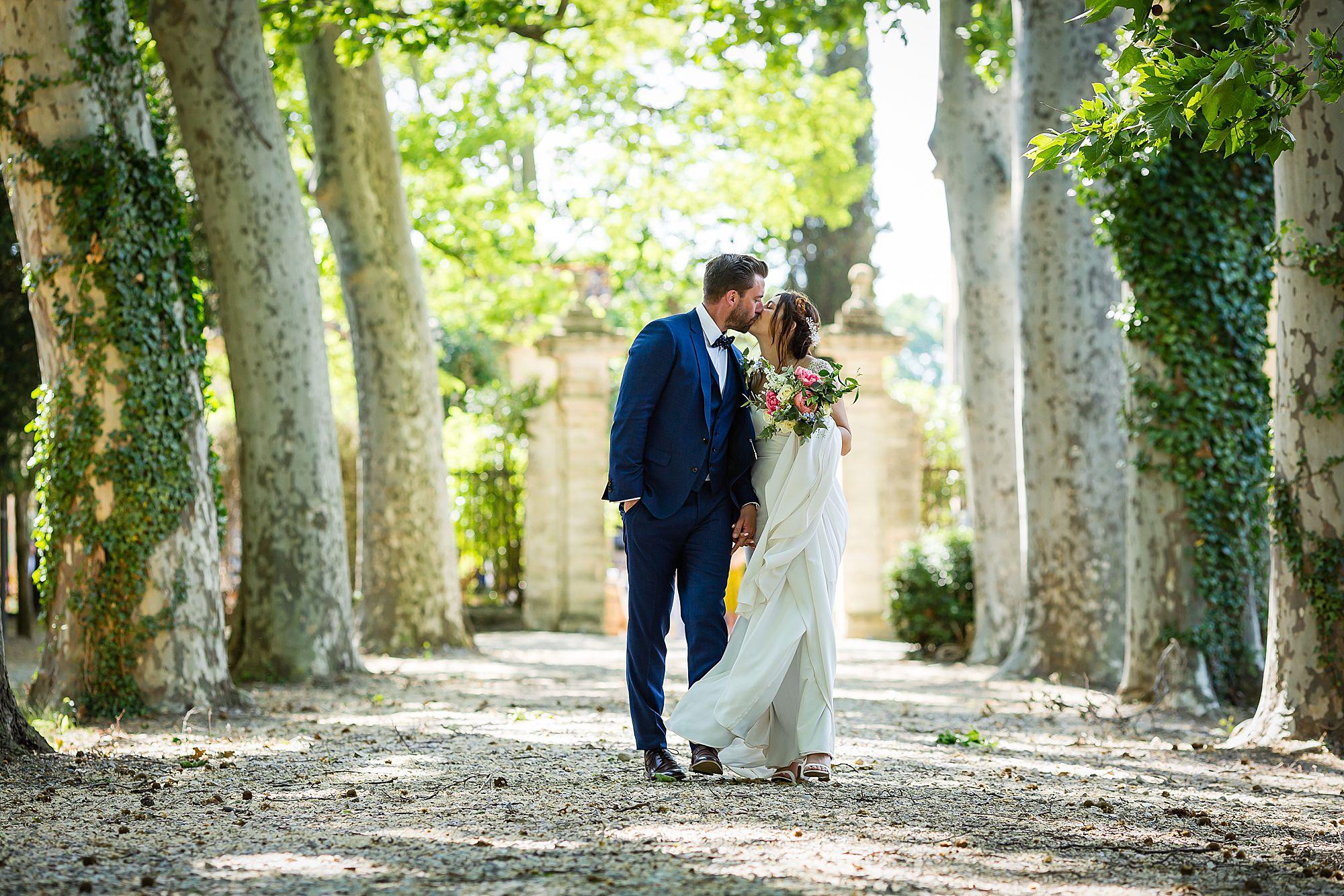 couple kiss under plain trees