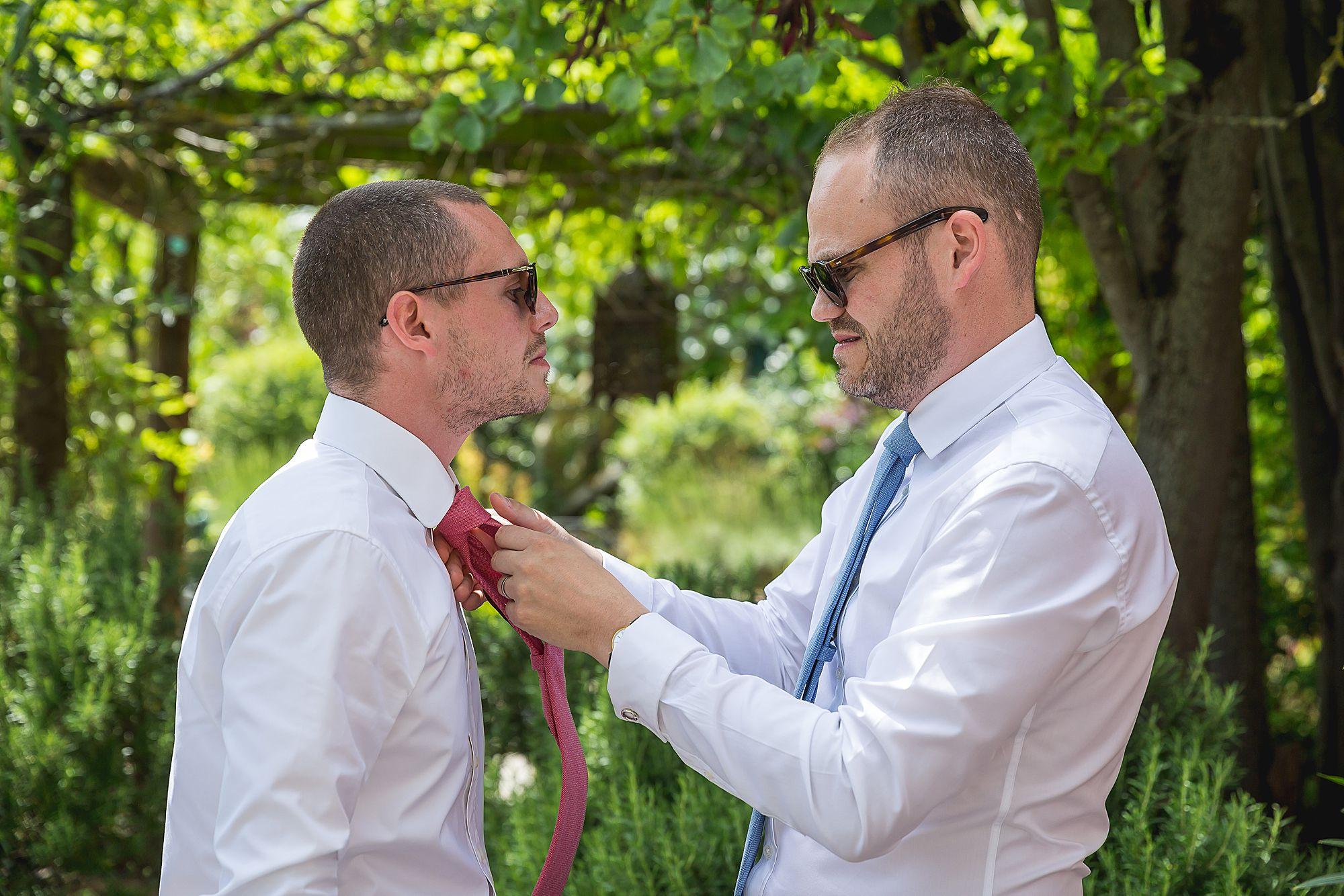 best man doing up grooms tie
