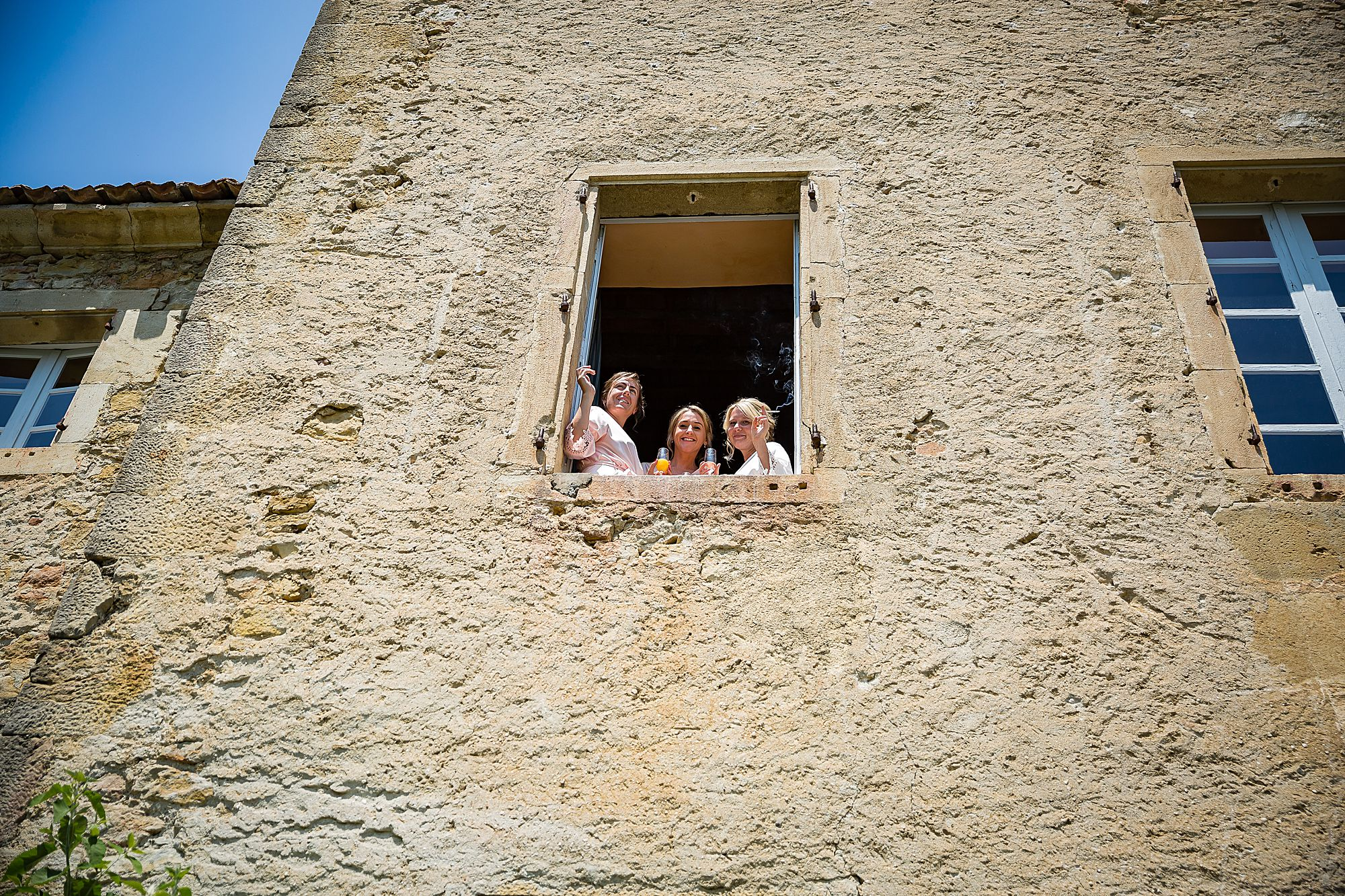 girls smoking out of window at Chateau de Queille Wedding.