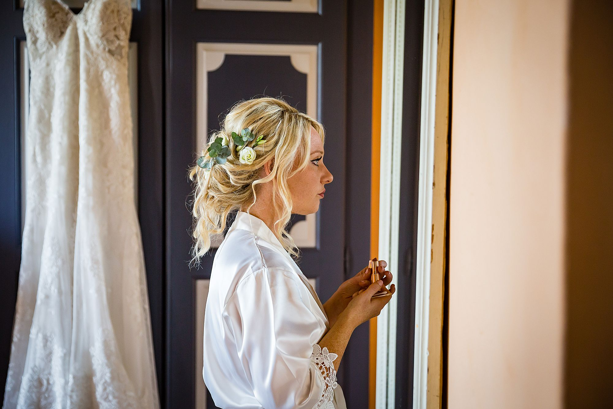 bride puts on lipstick for Chateau de Queille Wedding