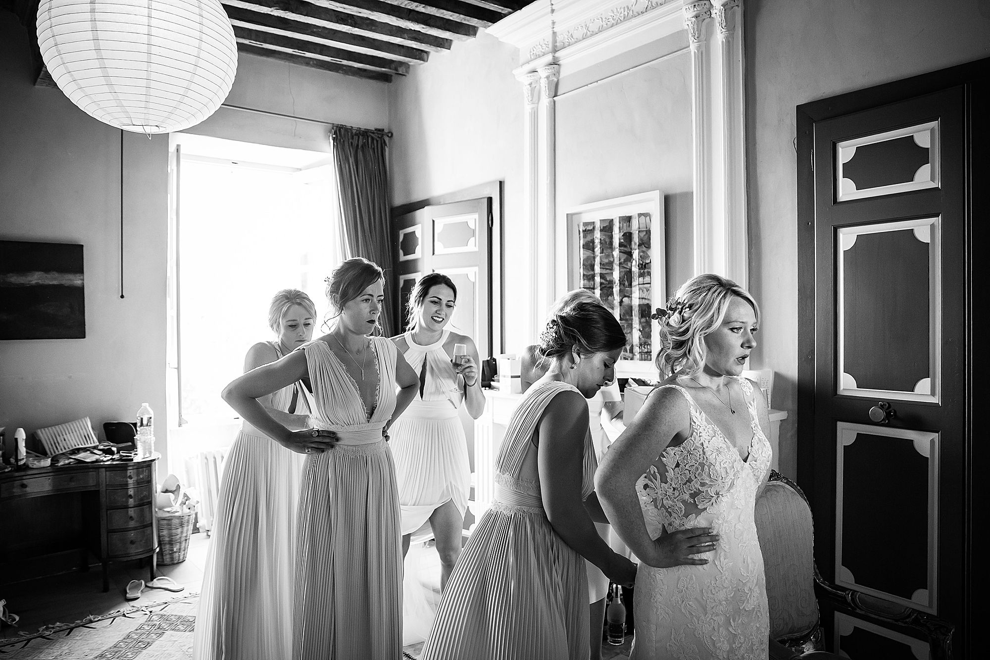 bride gets into dress for Chateau de Queille Wedding