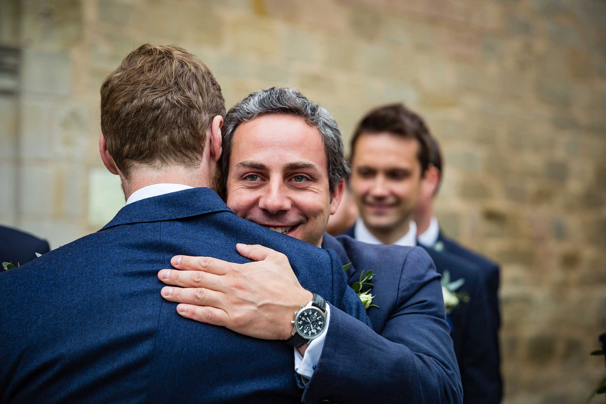 man hugs groom