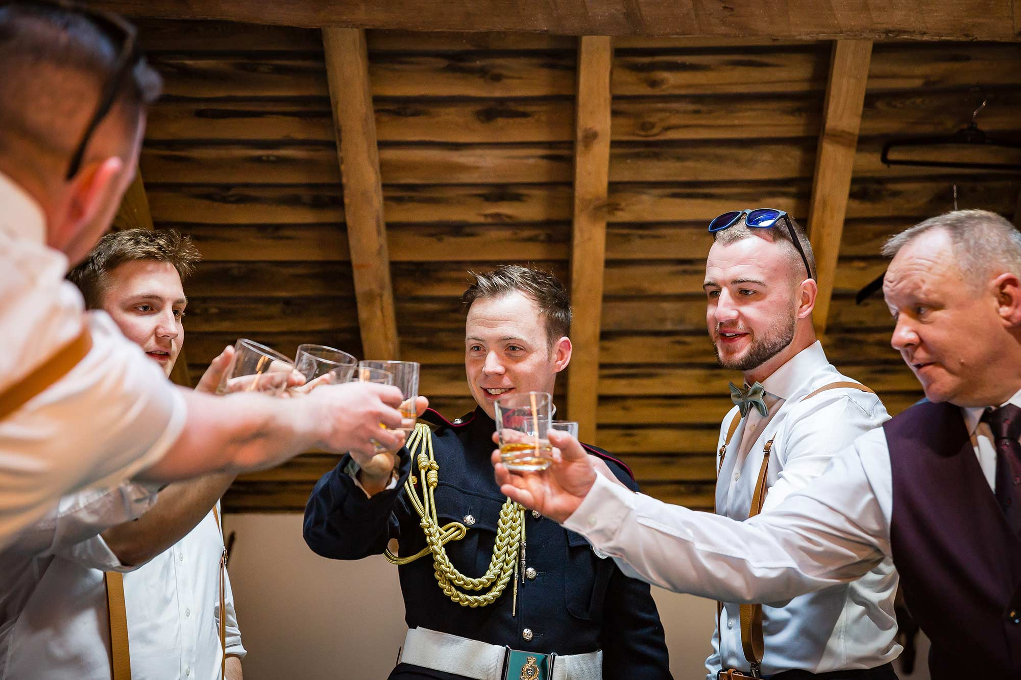 Guys toast a the wedding with whisky