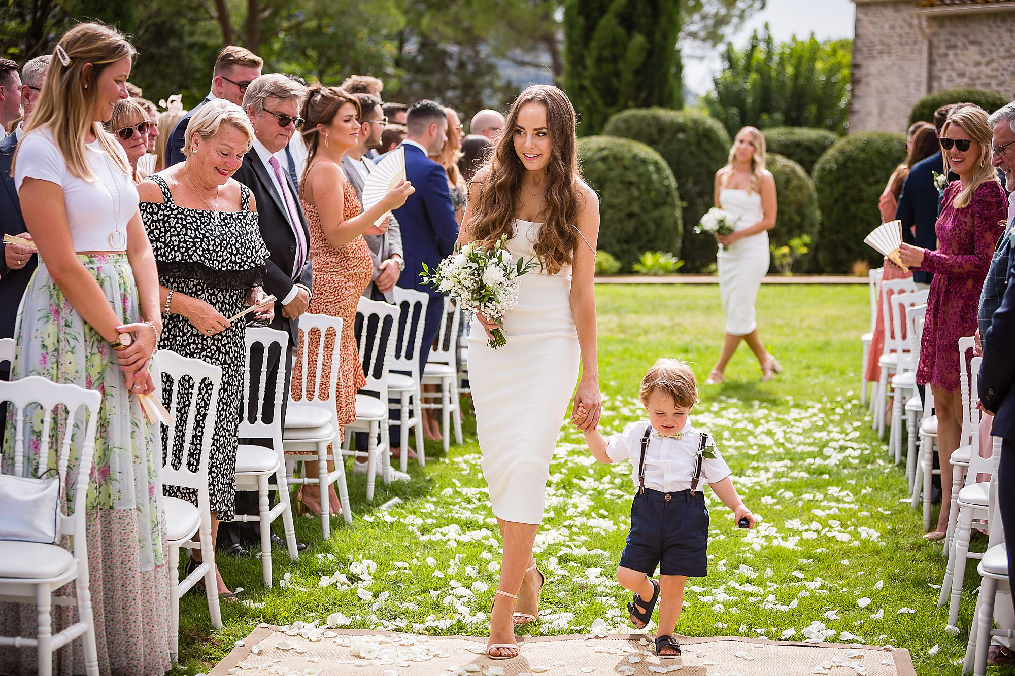 bridesmaid walks down the aisle with page boy