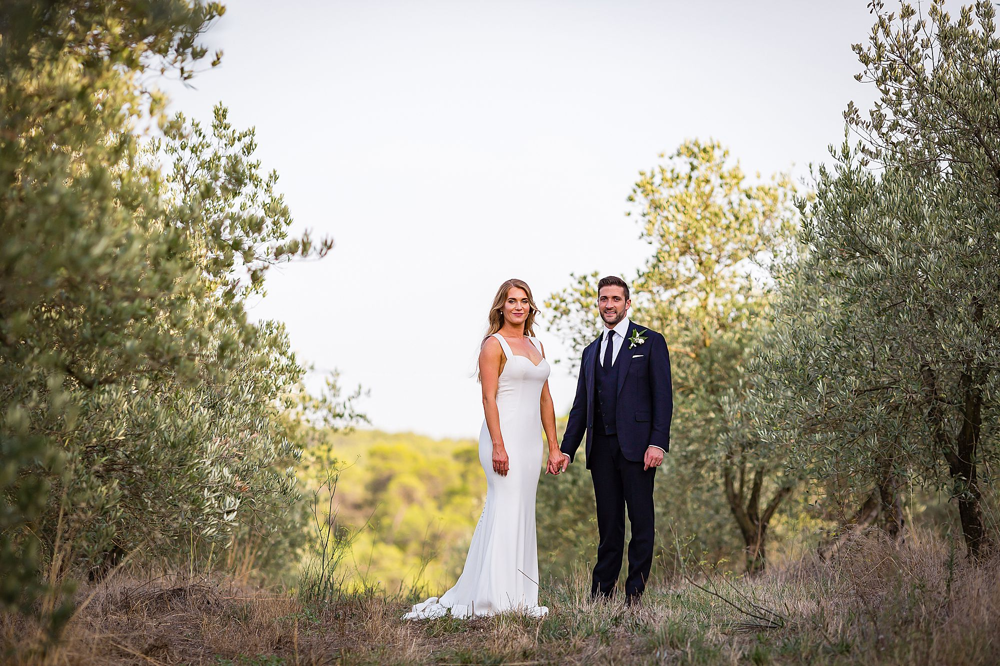 bride and groom standing in olive grove wedding