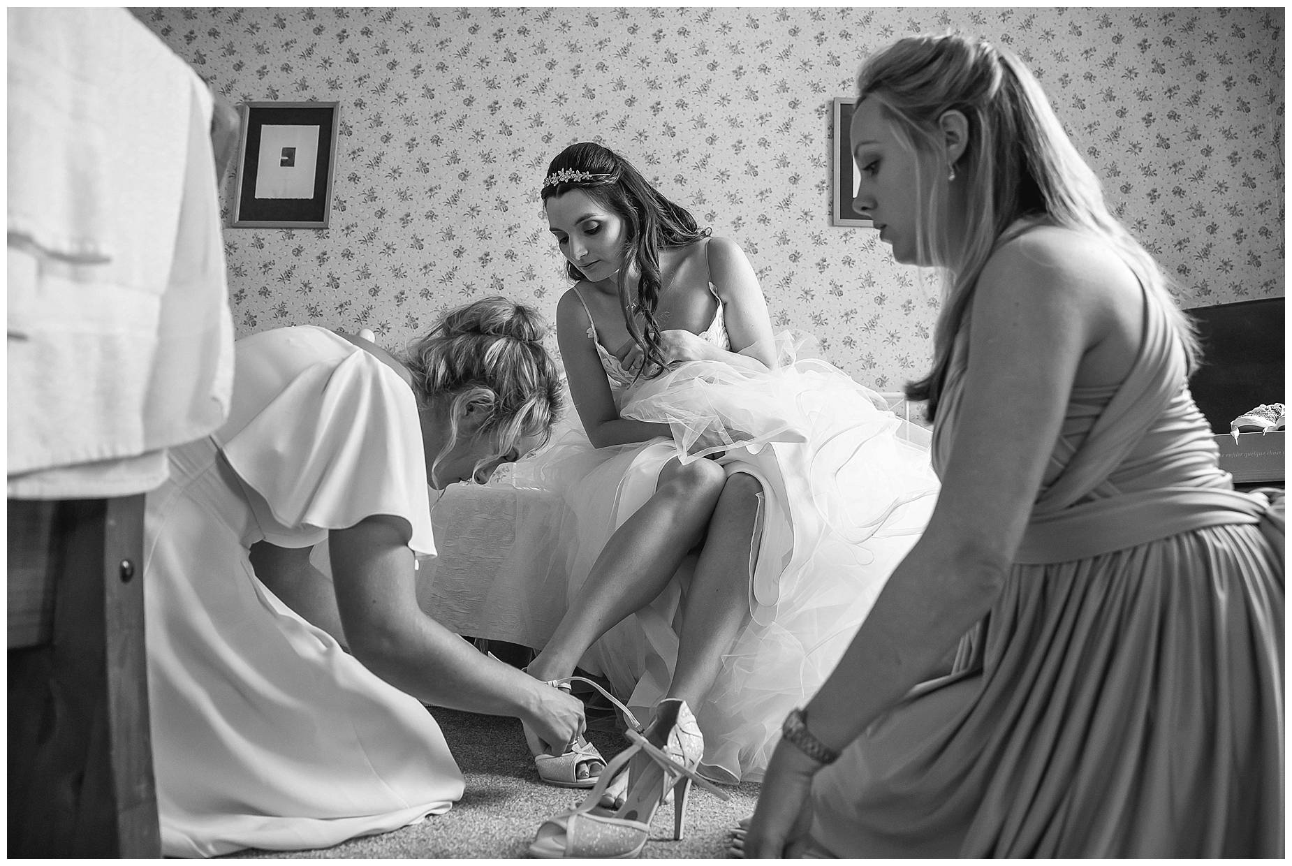 shoes being put on bride